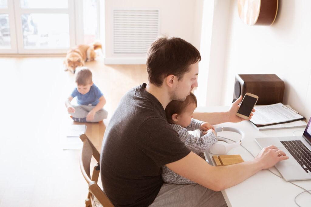 Padre millenial trabajando y cuidando su hijo